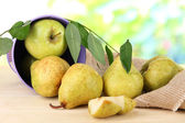 Pears in bucket on burlap on wooden table on nature background — Stock Photo