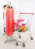Shopping cart with clothing, on gray wall background — Stock Photo