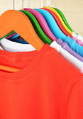 Different shirts on colorful hangers on light background — Zdjęcie stockowe