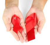 AIDS ribbon in hands isolated on white — Stock Photo