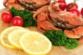 Boiled crabs with lemon slices and tomatoes, on wooden board, close up — Stock Photo