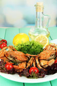 Boiled crabs on white plate with salad leaves and tomatoes,on wooden table, on bright background — Stock Photo