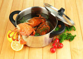 Composition with boiled crabs, pan and vegetables on wooden background — Stock Photo
