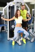 Meisje en trainer die zich bezighouden met simulator in gym — Stockfoto