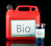 Bio fuels in canister and vial on black background — Stock Photo