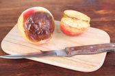 Ruttna äpplen på träplatta på bord — Stockfoto