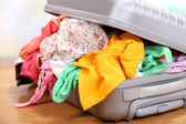 Suitcase with no neatly folded things on floor — Stock Photo