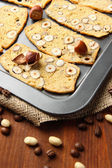 Biscotti with hazelnuts, on dripping pan, on wooden background — Stock Photo