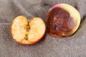 Rotten apples on sackcloth — Stock Photo
