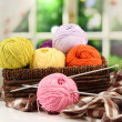 Multicolored clews in wicker basket with plaid closeup — Stock Photo #32220047