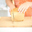 Woman slicing bread on chopping board, close up — Stock Photo