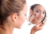Beautiful girl preens before small mirror isolated on white — Stock Photo