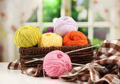 Multicolored clews in wicker basket with plaid closeup — Stock Photo