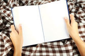 Book in hands on plaid background — Stock Photo