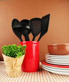 Plastic kitchen utensils in stand with clean dishes on tablecloth on brown background — Stock Photo