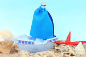 Blue toy ship on sand, on blue background — Stock Photo