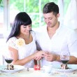 Man proposing and holding up an engagement ring his woman over restaurant table — Stock Photo