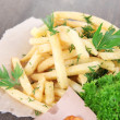 French fries on tracing paper on wooden table — Stock Photo