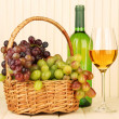 Ripe grapes in wicker basket, bottle and glass of wine, on light background — стоковое фото #32329007