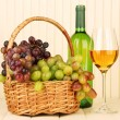 Ripe grapes in wicker basket, bottle and glass of wine, on light background — Stok fotoğraf