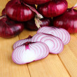Stock Photo: Fresh red onions on wooden table