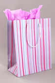Striped shopping bag on grey background — Photo