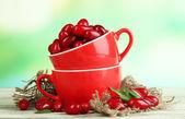 Färska cornel bär i röd koppar på träbord — Stockfoto
