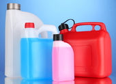 Liquids for car in canisters on blue background — Stock Photo