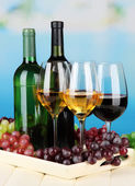 Wine bottles and glasses of wine on tray, on bright background — Stock Photo