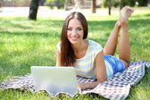 Beautiful young girl with laptop in park — Stock Photo