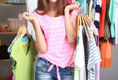 Beautiful girl with lots clothes in room background — Stock fotografie