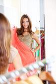 Bella ragazza cercando abito vicino specchio sullo sfondo della camera — Foto Stock