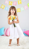 Little girl with flowers in room on grey wall background — Stok fotoğraf