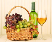 Ripe grapes in wicker basket, bottle and glass of wine, on light background — ストック写真