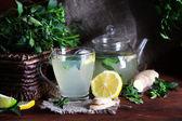 Bollitore e tazza di tè con zenzero sul tavolo di legno su sfondo luminoso — Foto Stock