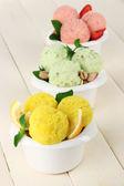 Scoop gelato gustoso in ciotole, sul tavolo di legno — Foto Stock