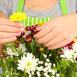 Florist makes flowers bouquet in wicker basket — Stock Photo