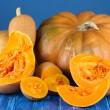 Ripe cut pumpkins on wooden table on blue background — Stock Photo #32332273