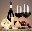 Refined still life of wine, cheese and grapes on wicker tray on wooden table on beige background — Stock Photo