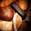 Much bread on wooden board — Stock Photo #32336941