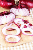 Fresh red onions on cutting board close up — Stock Photo