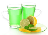 Two transparent cups of green tea with mint and lemon isolated on white — Stock Photo