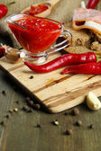 Composition with salsa sauce on bread,, red hot chili peppers and garlic, on sackcloth, on wooden background — Stock Photo