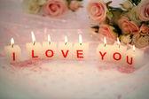 Svíčky s tištěnou znamení miluji tě, na pozadí barevných tkanin — Stock fotografie