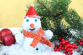 Beautiful snowman and Christmas decor, on golden background — Stock Photo