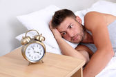 Handsome young man in bed — Stock Photo
