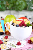 Oatmeal in cup with berries on napkins on wooden table on plant background — Stock Photo