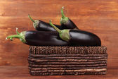 čerstvý lilek v proutěném koši na tabulce na dřevěné pozadí — Stock fotografie