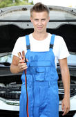 Young car mechanic with battery jumper cables to charge dead battery — Stockfoto