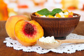 Sour cheese and pieces of fresh peach,on wooden table, on bright background — Stock Photo